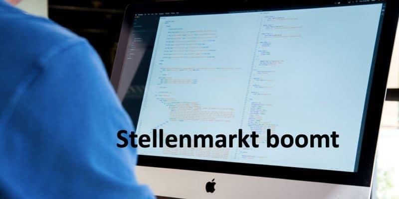 Person sitzt vor Computerbildschirm auf welchem Code zu sehen ist